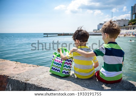 Two beautiful little boy sibling brothers in vest and shorts sitting on breakwater against the sea and shore in summer. Preschool children best friends enjoying summer vacations on sea. Royalty-Free Stock Photo #1933191755