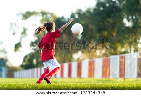 Girl kicks a soccer ball on a soccer field Royalty-Free Stock Photo #1933244348