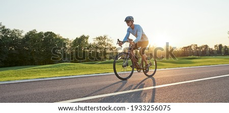 Full length shot of professional male racer in sportswear and helmet training, riding road bike on a cycle path in the park at sunset Royalty-Free Stock Photo #1933256075