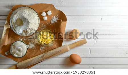A set of ingredients for baking confectionery confectionery made of flour, butter and eggs. Laying brown paper on a white wooden countertop. Royalty-Free Stock Photo #1933298351