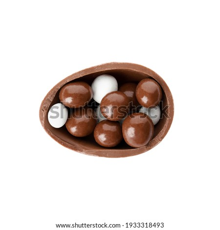 Half of tasty chocolate egg with candies on white background, top view Royalty-Free Stock Photo #1933318493