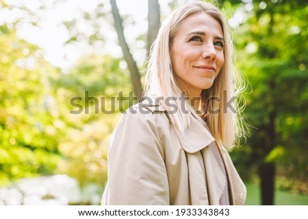 Caucasian blonde woman smiling happily on sunny summer or spring day outside walking in park. Royalty-Free Stock Photo #1933343843