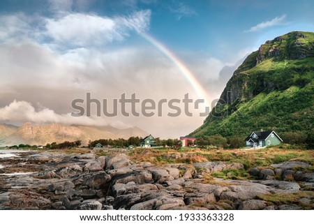 A rainbow juts out of the side of a mountain over the remote and colorful cabins of Lofoten, Norway. Coastal shot with rock beach and grasslands in the foreground Royalty-Free Stock Photo #1933363328