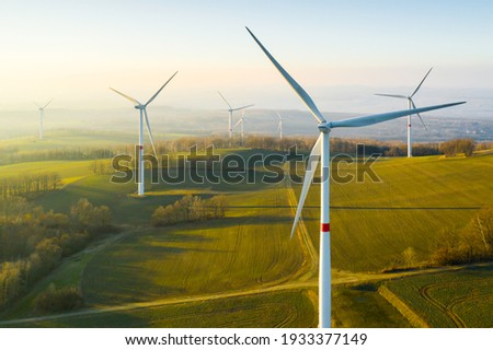 Panoramic view of wind farm or wind park, with high wind turbines for generation electricity with copy space. Green energy concept. Royalty-Free Stock Photo #1933377149