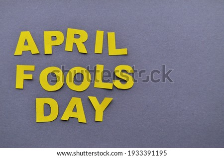 Image caption April Fools' Day yellow on a grey background close-up on the right copy space. High quality photo