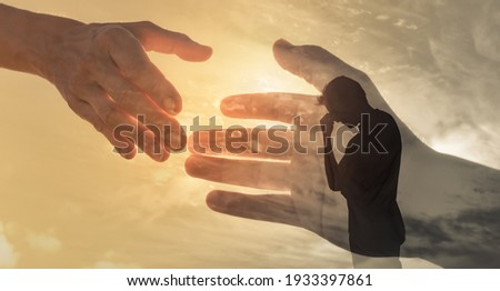 Man feeling sad and someone giving him a helping hand. Out of the darkness and into the light concept.  Royalty-Free Stock Photo #1933397861