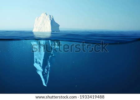 Iceberg in clear blue water and hidden danger under water. Iceberg - Hidden Danger And Global Warming Concept. Floating ice in ocean. Copyspace for text and design Royalty-Free Stock Photo #1933419488
