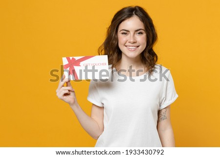 Young smiling happy caucasian student woman 20s wearing blank print design white basic t-shirt holding gift voucher flyer mock up look camera isolated on yellow orange color background studio portrait