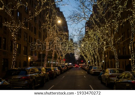 New York street night with Christmas string lighting on trees with side parking and traffic