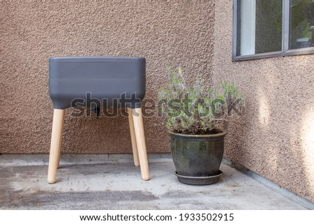 A vermicomposting system (worm composter) sits on an apartment balcony with other patio planters. Worms eat food scraps and produce worm castings and worm tea to be used as fertilizer