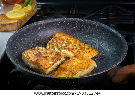 Fried halibut fish on pan with lemons on wooden cutting board, close up three pieces of filet halibut