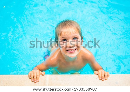 Funny portrait photo, happy smile mood lifestyle. Mischievous kid freckled boy wet head shoulders hands play swim in pool water. Face expression, gesture, look at camera. Childhood sport behaviour