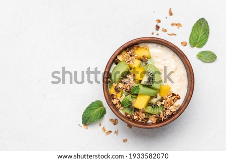 Mango yogurt with granola and kiwi in wooden bowl on white background. Healthy dairy product breakfast  Royalty-Free Stock Photo #1933582070