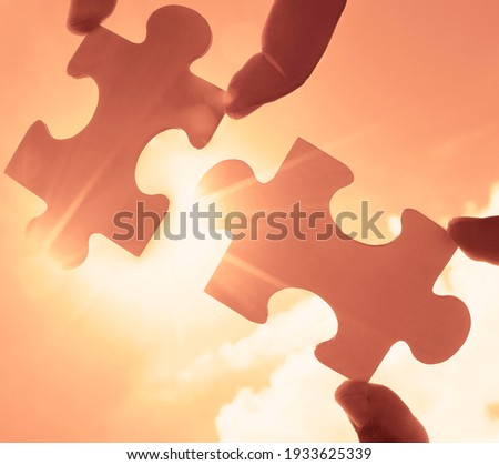 male Hand holding  jigsaw puzzle with  sunlight effect sky clouds. Strategies for business success. Collaboration and teamwork concept.  Royalty-Free Stock Photo #1933625339