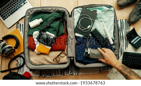 Man with tatted arm packs suitcase for adventure travel trip. Packing bag with camera, laptop, portable battery charger and electric toothbrush. Modern travel blogger concept Royalty-Free Stock Photo #1933678763