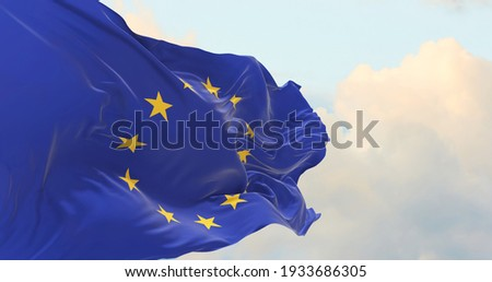 Flag of the European Union waving in the wind on flagpole against the sky with clouds on sunny day Royalty-Free Stock Photo #1933686305