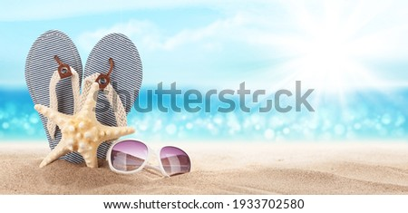 Flip flops, starfish and sunglasses on sunny sea beach with copy space. Travel vacation concept Royalty-Free Stock Photo #1933702580