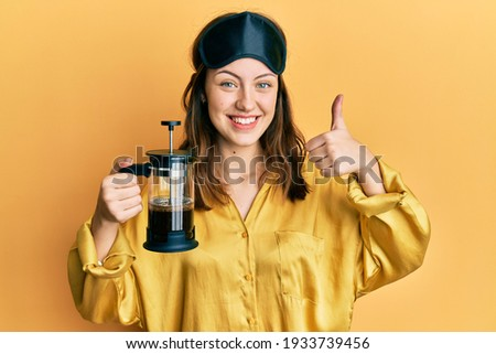 Young brunette woman wearing sleep mask holding coffee maker smiling happy and positive, thumb up doing excellent and approval sign