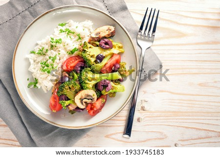 Vegetables like broccoli, tomatoes and olives with rice on a gray plate and a bright wooden table with napkin and fork, healthy vegetarian meal, copy space, high angle view from above, selected  Royalty-Free Stock Photo #1933745183
