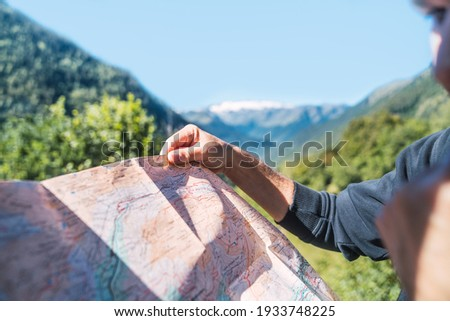 Anonymous man looking the travel route on a map in the mountain. Routes, excursions and mountain trails through nature in summer. Concept of exploring and live adventures traveling in nature. Royalty-Free Stock Photo #1933748225