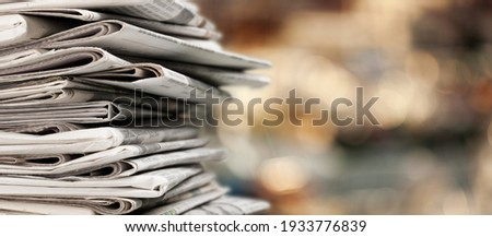 Pile of newspapers stacks on blur background Royalty-Free Stock Photo #1933776839