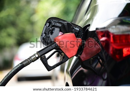 Refueling Car fill with petrol gasoline at  gas station and Petrol pump filling fuel nozzle in fuel tank of car Royalty-Free Stock Photo #1933784621
