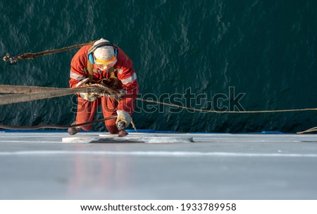 Seaman ship crew working aloft at height derusting and getting vessel ready for painting. Boat maintenance. Royalty-Free Stock Photo #1933789958