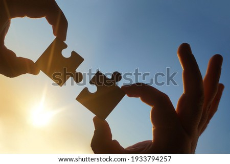 two hands of businessman to connect couple puzzle piece with sky background.Jigsaw alone wooden puzzle against sun rays.one part of whole.symbol of association and connection.business strategy Royalty-Free Stock Photo #1933794257