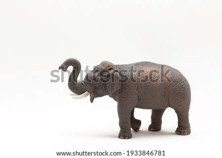 Realistic miniature elephant figure isolated on a white background. Elephant Toy. Copy space Royalty-Free Stock Photo #1933846781