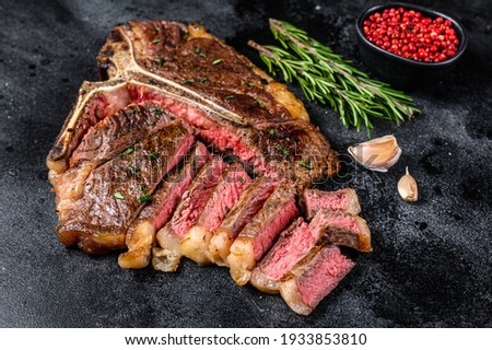 Grilled italian Florentine or t bone beef meat Steak. Black background. Top view. Royalty-Free Stock Photo #1933853810
