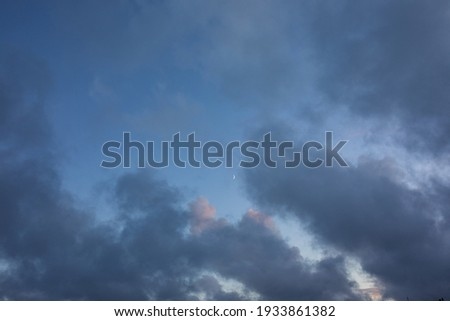 Dreamy, fairy tail like, blue and purple clouds on a sunset sky with bright moon