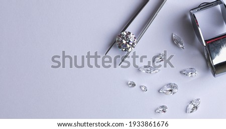 Layout of round cut diamond on tweezers with other diamonds of different cuts on light background with copy space top view. Royalty-Free Stock Photo #1933861676