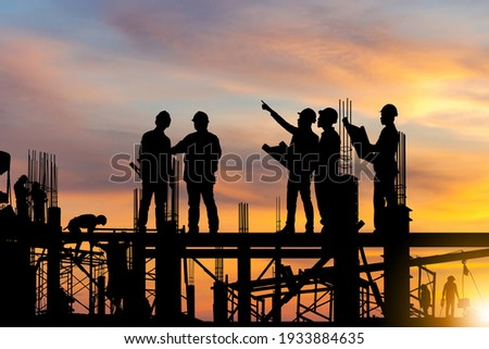 Silhouette of Engineer and worker on building site, construction site at sunset in evening time. Royalty-Free Stock Photo #1933884635