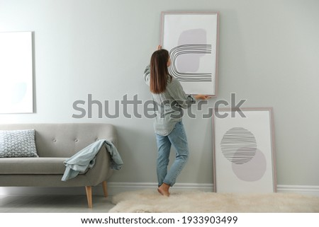 Woman hanging picture on wall in room. Interior design