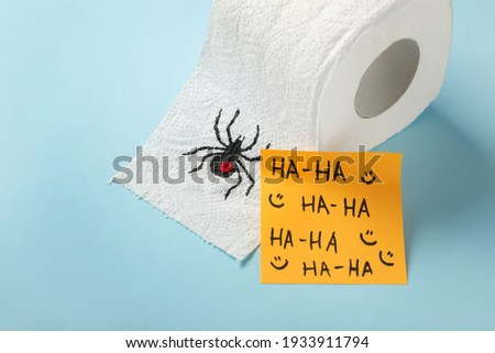 Toilet paper roll with drawn spider and words Ha-Ha  on light blue background. Celebrating April Fool's Day Royalty-Free Stock Photo #1933911794