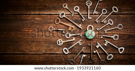 Vintage rusty padlock surrounded by group of old keys on a weathered wooden background. Internet security and data protection concept, blockchain and cybersecurity. Lockdown. Escape route and room  Royalty-Free Stock Photo #1933921160