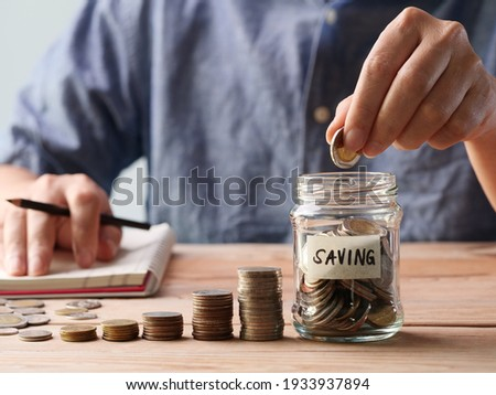A man hand putting coins in a glass jar. Concept of retirement, save money and cash, finance, investing, growth management, business, financial planning. Royalty-Free Stock Photo #1933937894