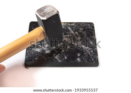 A smashed digital tablet isolated on white with a sledgehammer held above it. Perspective is from above. Royalty-Free Stock Photo #1933955537