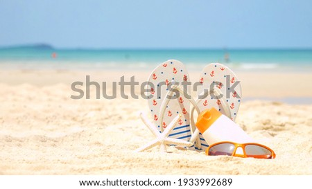 Summer assessorieses. Planing to travel with sunblock and sandal on the beautiful beach and blue sky background. Tropical fashion. Summer Fashion on holiday concept.  Royalty-Free Stock Photo #1933992689
