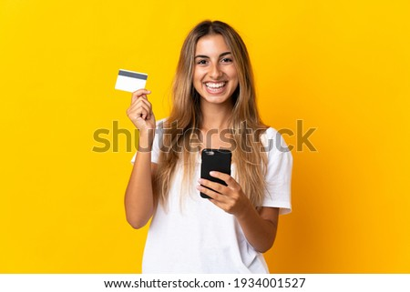 Young hispanic woman over isolated yellow background buying with the mobile with a credit card
