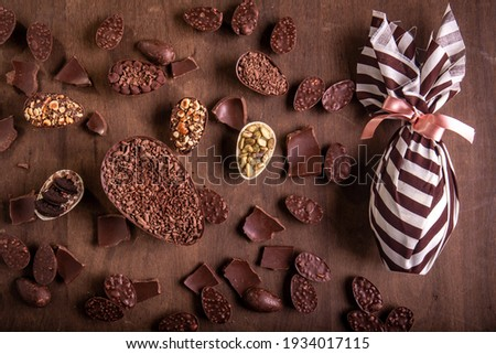 Top view of lots of mini stuffed chocolate easter eggs, cracked chocolates and a wrapped easter egg on a wooden table. Royalty-Free Stock Photo #1934017115
