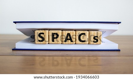 SPACs symbol. Wooden cubes with words 'SPACs, special purpose acquisition companies' in book on beautiful white background, copy space. Wooden table. Business and SPACs concept.