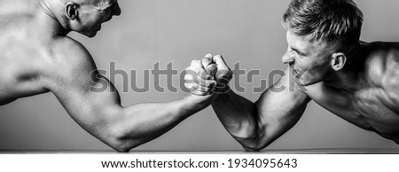 Arm wrestling. Two men arm wrestling. Rivalry, closeup of male arm wrestling. Two hands. Men measuring forces, arms. Hand wrestling, compete. Hands or arms of man. Muscular hand. Black and white.