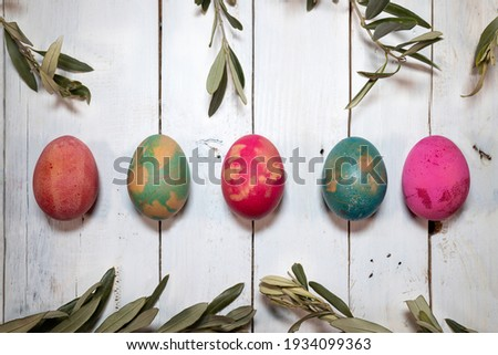 Two Easter symbols: eggs and olive twigs. Five coloured eggs with olive twigs around them on a shabby chic wooden table.  Royalty-Free Stock Photo #1934099363