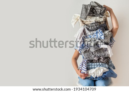 Surprised woman holding metal laundry basket with messy clothes on white background. Laundry. Isolated housewife. Copy space. Textile. Dirty wardrobe. Decluttering concept. Disorganized wife. Royalty-Free Stock Photo #1934104709