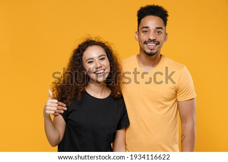 Young couple two american friends family happy satisfied smiling african man woman 20s together in black t-shirt hug girlfriend show thumb up like gesture isolated on yellow background studio portrait