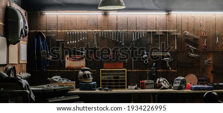 Workshop scene. Old tools hanging on wall in workshop, Tool shelf against a table and wall, vintage garage style Royalty-Free Stock Photo #1934226995