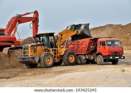 Excavator loading tipper truck on a construction site #193425245