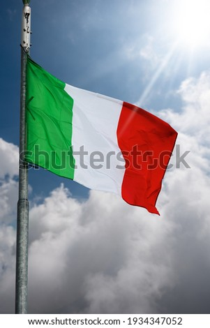 Closeup of a national Italian flag with flagpole, blowing in the wind on a blue sky with clouds and Sunbeams. Royalty-Free Stock Photo #1934347052