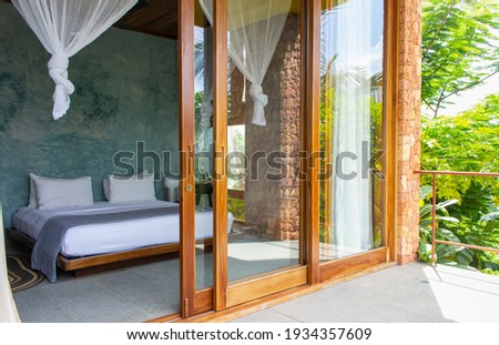 Luxury hotel room with mosquito net and open terrace. Comfortable interior of tropical hotel. Cozy and elegant bedroom design. Summer travel in tropics. Tourist resort. Bed with baldachin. Modern home Royalty-Free Stock Photo #1934357609